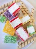 Doce de fruta colorido cortado nas partes em uma placa branca Imagem de Stock Royalty Free