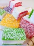 Doce de fruta colorido cortado nas partes em uma placa branca Fotografia de Stock Royalty Free