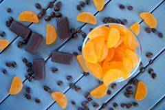 Doce de fruta da tangerina, grãos de café e doces de chocolate em uma tabela feita de placas de madeira pintadas A combinação de  fotos de stock royalty free
