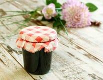 Doce de fruta no vidro e nas flores em de madeira Imagem de Stock