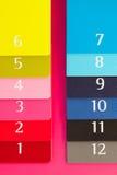 Doce diversos diarios del color en un escritorio de madera rosado Imagen de archivo libre de regalías