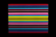 Doce diversos diarios del color en una tabla de cristal negra Imagenes de archivo
