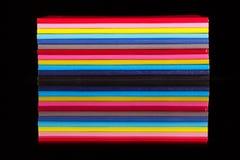 Doce diversos diarios del color en una tabla de cristal negra Imágenes de archivo libres de regalías
