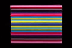 Doce diversos diarios del color en una tabla de cristal negra Imagen de archivo libre de regalías