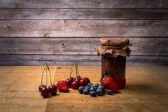 Doce e frutos no fundo de madeira fotografia de stock royalty free