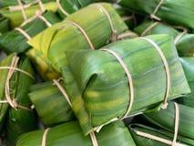 Doce tailandês com a banana do arroz e o leite de coco cobertos pela folha da banana e o córrego da fervura ou o Khao Tom Mat imagens de stock royalty free