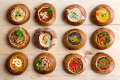 Doce variedades de la sopa servidas en cuencos del pan imágenes de archivo libres de regalías