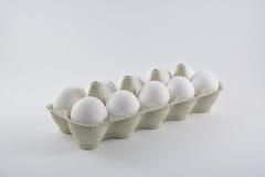 Docena huevos blancos del pollo en una caja de cartón Fotografía de archivo