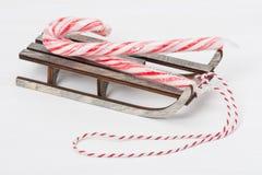 Doces Cane On Wooden Sledge do Natal branco foto de stock