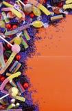 Doces coloridos brilhantes no fundo de madeira alaranjado Imagem de Stock