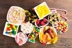 Doces coloridos diferentes no prato branco sobre a tabela de madeira Fotos de Stock Royalty Free