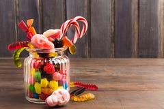 Doces coloridos diferentes nos crânios doces do woth de vidro do frasco, reat Imagens de Stock Royalty Free