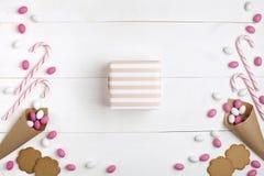 Doces coloridos do quadro, pirulitos listrados, cookies, e atual no centro Vista superior, fundo de madeira branco fotografia de stock royalty free