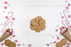 Doces coloridos do quadro, pirulitos listrados e cookies Vista superior, fundo de madeira branco, espaço da cópia Rosa vermelha fotos de stock