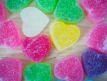 Doces coloridos dos corações na madeira para o fundo dos Valentim Fotografia de Stock Royalty Free
