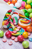 Doces coloridos e pastilha elástica em uns sacos de papel Imagens de Stock