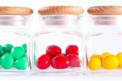Doces coloridos nas garrafas de vidro Fotos de Stock Royalty Free