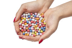 Doces coloridos nas mãos fêmeas Fotografia de Stock