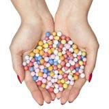 Doces coloridos nas mãos fêmeas Imagens de Stock Royalty Free
