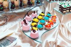 Doces cor-de-rosa vermelhos amarelos azuis em um suporte de vidro no casamento candybar Imagens de Stock