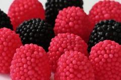 Doces da geleia sob a forma das framboesas, vermelho e preto em um fundo branco foto de stock