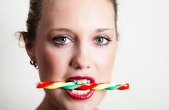Doces da terra arrendada da mulher nova em seus dentes Imagem de Stock