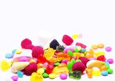 Doces de açúcar coloridos múltiplos no fundo branco com espaço para o texto fotografia de stock