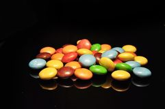 Doces de chocolate coloridos isolados no fundo preto foto de stock