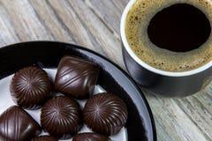Doces de chocolate em uma placa e em uma xícara de café em uma superfície de madeira fotografia de stock