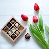 Doces de chocolate na caixa Caixa e tulipas dos doces para o presente romântico no fundo branco fotografia de stock