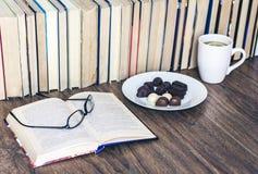 Doces de chocolate na placa e no copo brancos do ch? com o lim?o com a pilha de livros no fundo fotos de stock
