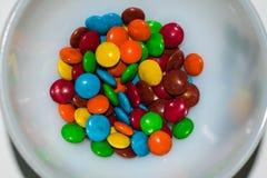 Doces de chocolate revestidos coloridos em uma bacia branca foto de stock royalty free