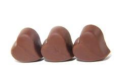 Doces de chocolate três na forma do coração fotografia de stock