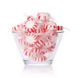Doces de pastilha de hortelã na bacia de vidro no branco. Doces listrados vermelhos do Natal da hortelã Imagem de Stock
