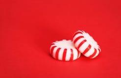 Doces de pastilha de hortelã sobre o fundo vermelho do Natal Imagem de Stock Royalty Free