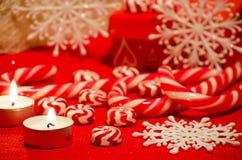 Doces do caramelo, flocos de neve e velas vermelhos e brancos no b vermelho Fotografia de Stock
