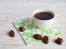 Doces do chocolate e uma xícara de café Fotos de Stock