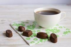 Doces do chocolate e uma xícara de café Imagem de Stock Royalty Free