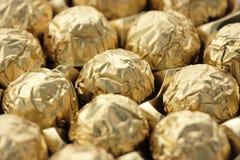 Doces do chocolate na folha dourada Fotografia de Stock Royalty Free