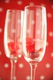 Doces do coração em flautas do vinho contra às bolinhas Fotografia de Stock