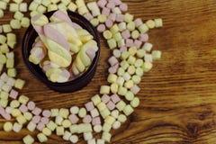 Doces do marshmallow colocados em uma cesta em torno dos outros doces Dia do ` s do Valentim e conceito do amor no fundo de madei Fotos de Stock