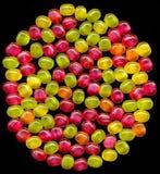 Doces doces coloridos brilhantes isolados em um fundo preto Imagem de Stock