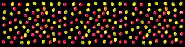 Doces doces coloridos brilhantes isolados no fundo preto Imagens de Stock Royalty Free