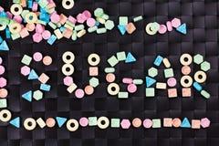 Doces doces coloridos com um açúcar da palavra no fundo preto Imagens de Stock