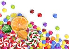 Doces dos doces com pirulito, suco de laranja, bubblegum em um fundo branco Imagem de Stock