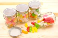 Doces dos frascos e de feijões de geléia derramados Fotografia de Stock Royalty Free