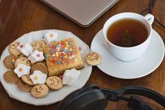 Doces e cookies com caras alegres, um copo do chá perfumado atrás de um portátil e fones de ouvido sem fio em uma tabela de mogno Fotos de Stock Royalty Free
