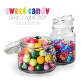 Doces e goma diferentes da cor nos frascos de vidro Fotos de Stock