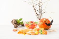 Doces em uns vasos na tabela decorada para Dia das Bruxas Fotos de Stock Royalty Free