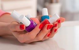 doces Multi-coloridos da geleia nas mãos com um verniz para as unhas brilhante Fotos de Stock